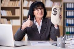 Den mogna affärskvinnan som arbetar i kontoret arkivbild
