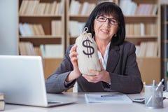 Den mogna affärskvinnan som arbetar i kontoret royaltyfria foton