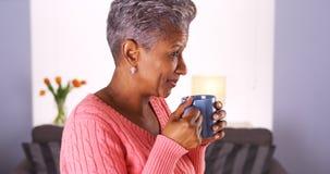 Den mogna afrikanska kvinnan som ler med kaffe, rånar fotografering för bildbyråer