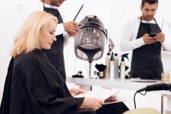 Den mogna attraktiva kvinnan på par med frisören väljer stil för framtida frisyrer i skönhetsalong Royaltyfri Bild
