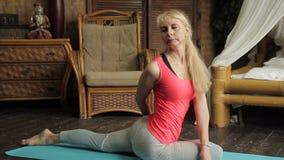 Den mogna blonda damen gör yogaövningar i tappningsovrummet lager videofilmer
