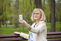 Den mogna härliga kvinnan läser meddelandet på telefonen royaltyfri fotografi