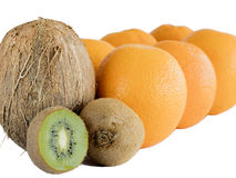 Den mogna kiwin, den bruna kokosnöten och en hög av apelsinen på en vit isolerade bakgrund arkivbild