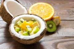 Den mogna kokosnöten knäckte i halva i halv kokosnötfruktsallad med orange skivor av bananen och kiwi Arkivfoton