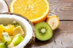 Den mogna kokosnöten knäckte i halva i halv kokosnötfruktsallad med orange skivor av bananen och kiwi Royaltyfri Fotografi