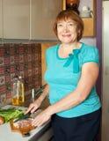 Den mogna kvinnan är matlagningmeat Royaltyfri Fotografi