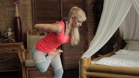 Den mogna kvinnan har yogautbildning i hennes rum i tappningstil stock video
