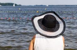 Den mogna kvinnan i en svartvit hatt på sjökusten observerar vatten Arkivbilder