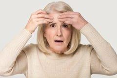 Den mogna kvinnan känner rubbning om begreppsmässig bild för ansikts- skrynklastudio arkivbild