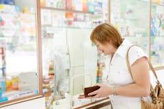 Den mogna kvinnan köper droger Royaltyfri Fotografi