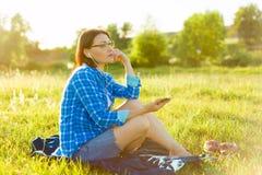 Den mogna kvinnan lyssnar till musik, en audiobook på hörlurar, kopplar av i natur Arkivfoto