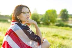 Den mogna kvinnan lyssnar till musik, en audiobook på hörlurar, kopplar av i natur På skuldraamerikanska flaggan Royaltyfri Bild