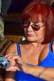 Den mogna kvinnan rymmer kameran Arkivbild