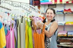 Den mogna kvinnan väljer klänningen på shoppar royaltyfri bild
