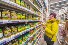 Den mogna kvinnan väljer på burk grönsaker i en supermarket royaltyfri bild