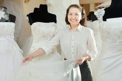 Den mogna kvinnan visar den brud- klänningen Royaltyfri Bild