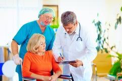 Den mogna kvinnliga patienten på rullstolen lyssnar till doktorsperscriptionläkarbehandlingen Arkivbild