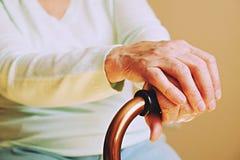Den mogna kvinnlign i äldre omsorglätthet får hjälp från sjukhuspersonalsjuksköterska Slut upp av åldriga rynkiga händer av den h royaltyfri fotografi
