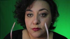 Den mogna latina kvinnan sätter på exponeringsglas arkivfilmer