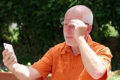 Den mogna mannen har problem med hans synförmåga för att läsa på hans sma Royaltyfria Foton