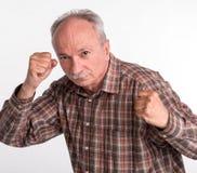 Den mogna mannen i boxare poserar med lyftta nävar Fotografering för Bildbyråer