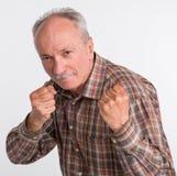 Den mogna mannen i boxare poserar med lyftta nävar Royaltyfri Fotografi