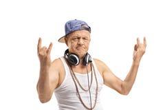 Den mogna mannen med hörlurarframställning vaggar handgester arkivfoton