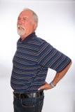 Den mogna mannen med tillbaka smärtar Arkivfoto