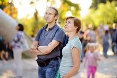 Den mogna mannen och kvinnan att sköta deras sonson nära lekplats parkerar offentligt på den soliga sommardagen arkivbild