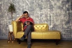 Den mogna mannen sitter på soffan som läser en tidskrift royaltyfri foto