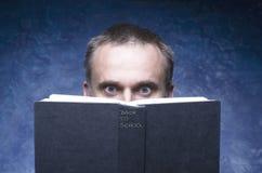 Den mogna mannen som fokuserades och hakades av boken som läser den öppna boken, förvånade den unga mannen som förbluffar synar s Arkivbilder
