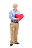 Den mogna mannen som rymmer en röd hjärta, formade kudden Royaltyfri Fotografi