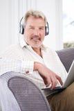 Den mogna mannen strömmar musik från bärbara datorn till trådlös hörlurar Arkivfoton