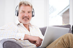 Den mogna mannen strömmar musik från bärbara datorn till trådlös hörlurar Royaltyfri Bild