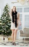 Den mogna mellersta ålderkvinnan i rik inre dekorerade för jul Härlig blond kvinnlig som hemma ler Vänta på Royaltyfria Bilder