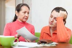 Den mogna modern grälar på dottern för räkningar eller krediteringar Arkivfoto