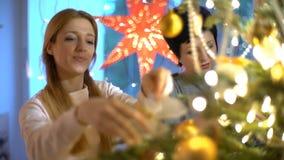 Den mogna modern och hennes vuxna dotter dekorerar julgranen inomhus stock video