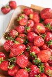 Den mogna röda jordgubben på ett magasin på en vit bakgrund, beskådar stort Royaltyfria Foton