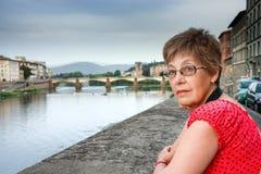 Den mogna turist- kvinnan blir mot bron över den Arno floden i Florence Royaltyfri Fotografi