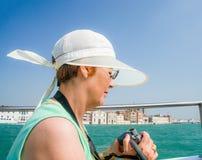 Den mogna turist- kvinnan seglar på fartyget i Venedig Fotografering för Bildbyråer