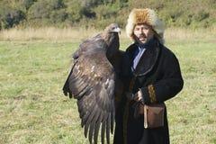 Den mongoliska jägaren i traditionell klänning rymmer den guld- örnen circa Almaty, Kasakhstan Arkivbild