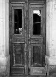 Den monokromma bilden av en bruten gammal dubbel dörr i ett övergett övergivet hus med brutna fönster och urblekt skalning målar royaltyfri fotografi