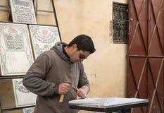 Den moroccan gravören inristar gravskriften på marmorn Royaltyfria Bilder
