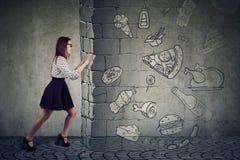 Den motiverade kvinnan som motstår frestelse av att äta den snabba foten och att välja som är bättre, bantar arkivbild