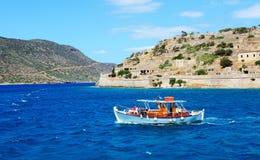 Den motoriska yachten med turister är nära den Spinalonga ön Arkivbilder