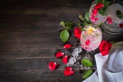 Den mousserande kallt vattendetoxen med rosen och is p? tr?tabellen d?r ?r rosa, diferanceexponeringsglas, samma objekt och is so royaltyfri bild