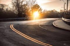 Den mörka asfaltvägen med ljusa gula linjer buktar under solnedgång Fotografering för Bildbyråer