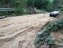 Den Muddy Dirt vägen av stigande klättring är barriären gjorda problem av loppet royaltyfri foto