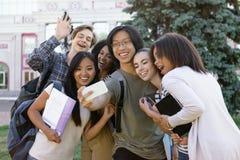 Den multietniska gruppen av unga lyckliga studenter gör selfie utomhus arkivfoton
