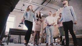 Den multietniska gruppen spelar med bollen i modernt kontor Lyckliga unga anställda tycker om sund ultrarapid för kontorsatmosfär arkivfilmer